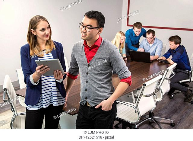 Two young millennial business professionals looking at a tablet while working together in a conference room with their peers; Sherwood Park, Alberta, Canada