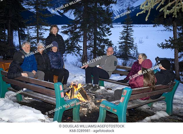 People sit by a fire in Jasper National Park, Alberta, Canada