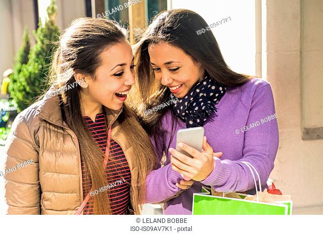 Young female adult twins in city with shopping bags laughing at smartphone text