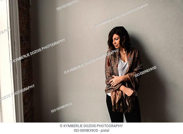 Woman standing with arms crossed, grey wall background