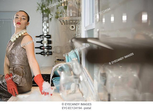 Young woman holding soap sud by sink in kitchen