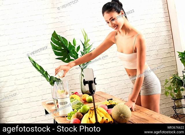 Young women live online use the juicer