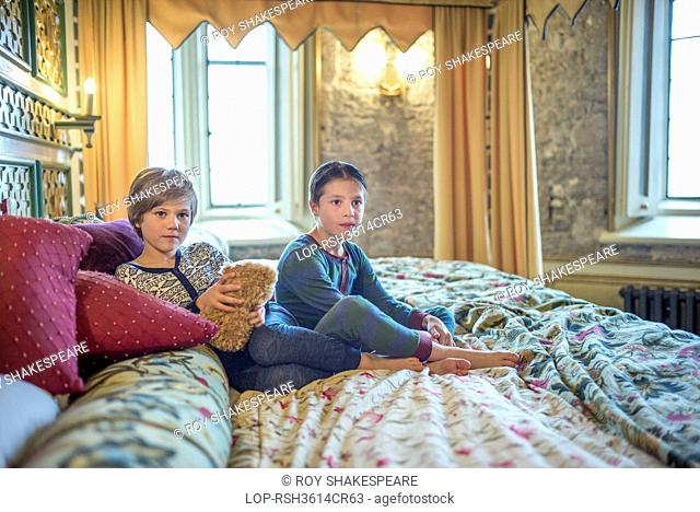 England, Gloucestershire, Thornbury. Two boys in onesies on the biggest hotel bed in Europe at Thornbury Castle