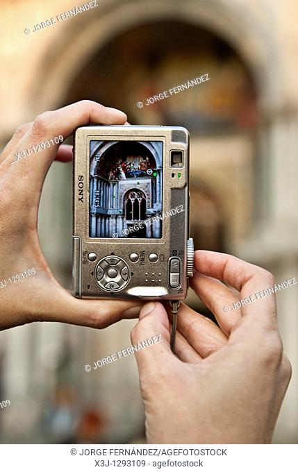 Cloe up of the hands of a woman taking a picture of the frescoes of San Marcos Cathedral, Venice, Italy, Europe