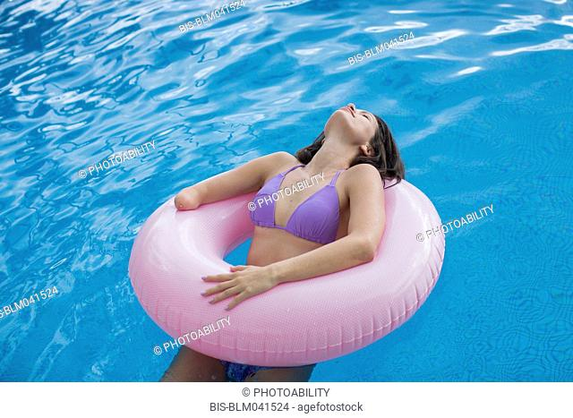 Mixed race amputee woman swimming in pool