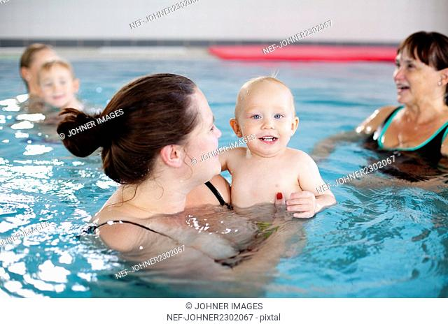 Mother holding baby boy in swimming pool