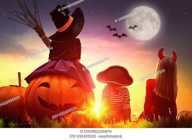 Happy brother and two sisters on Halloween. Funny kids in carnival costumes outdoors. Cheerful children and pumpkins on sunset background