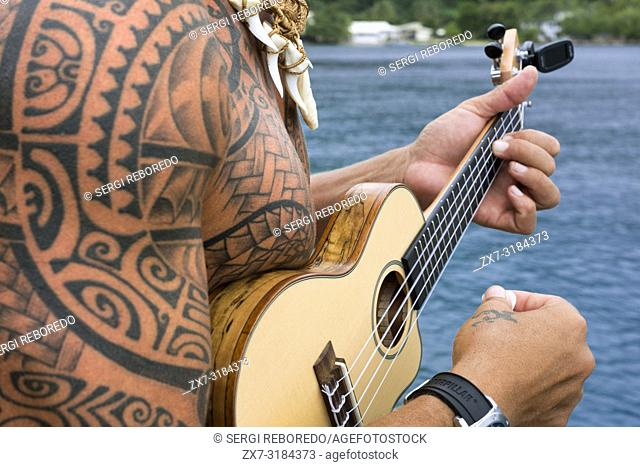 Local tattooed person playing the ukulele in Huahine, Society Islands, French Polynesia, South Pacific