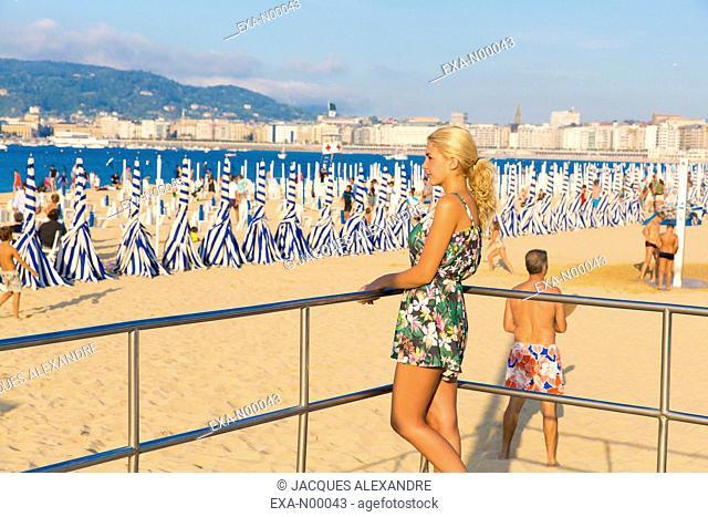 Woman looks at La Concha beach, San-Sebastian Bay, Gipuzkoa, Basque Country, Spain
