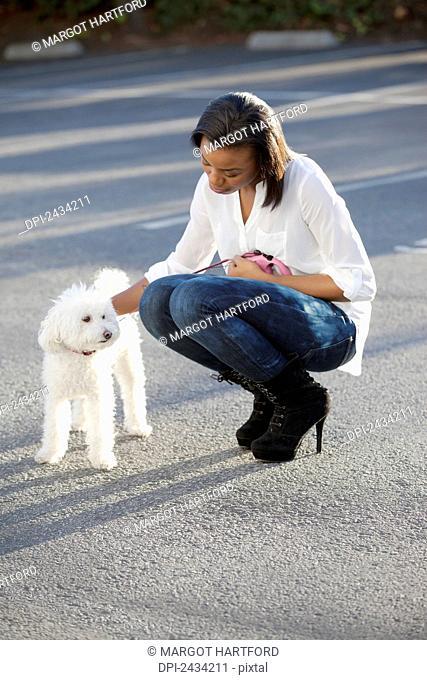 A woman walking her white dog; San Francisco, California, United States of America