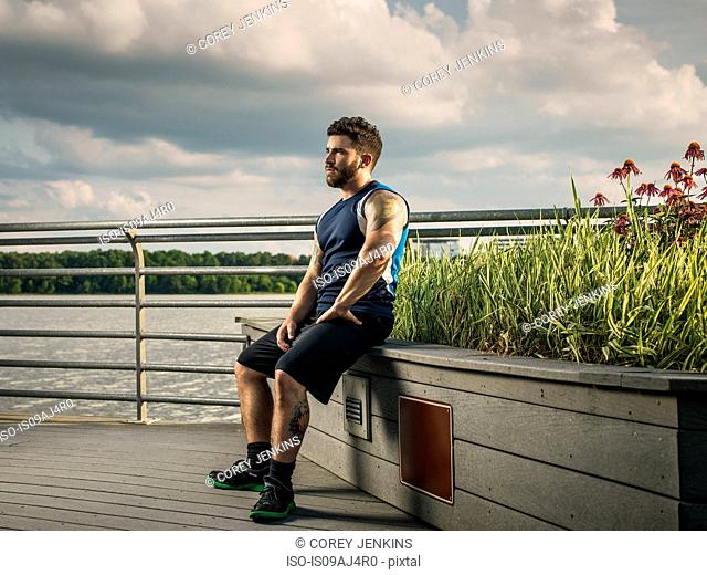 Young man taking a break from training on lake pier seat