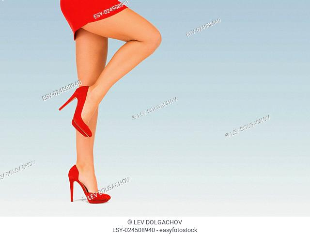 people, fashion and footwear concept - close up of woman legs in red high heeled shoes over blue background