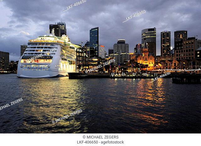 Skyline of the Central Business District and cruise ship at the Overseas Passenger Terminal in the evening, The Rocks, Sydney Harbour, Sydney, New South Wales
