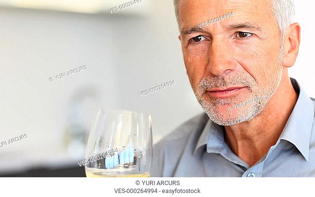 A senior man enjoying a glass of white wine with a smile