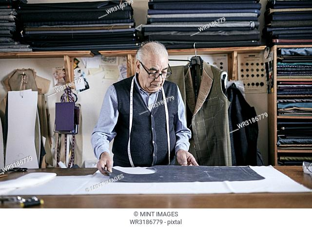 Tailor with measuring tape around neck working on a cut piece of fabric