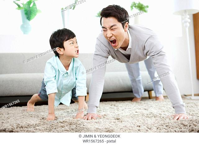 a father and a son working out in the living room