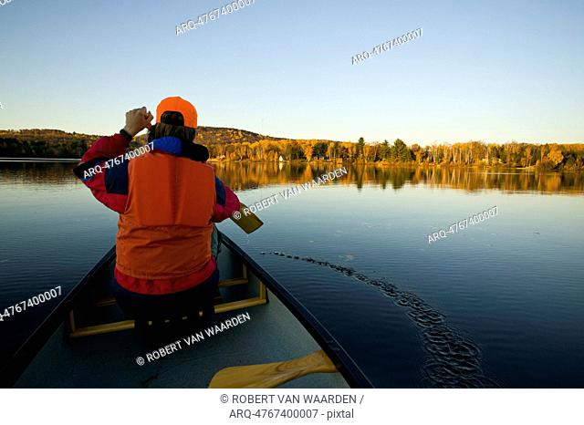 A boy in a life jacket paddles a canoe on a lake near Barry's Bay, Ontario, Canada