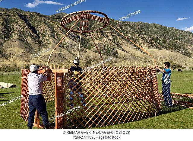 Kazakh men setting up a yurt in pasture of Chilik river valley with Kungey Alatau mountains Saty Kazakhstan