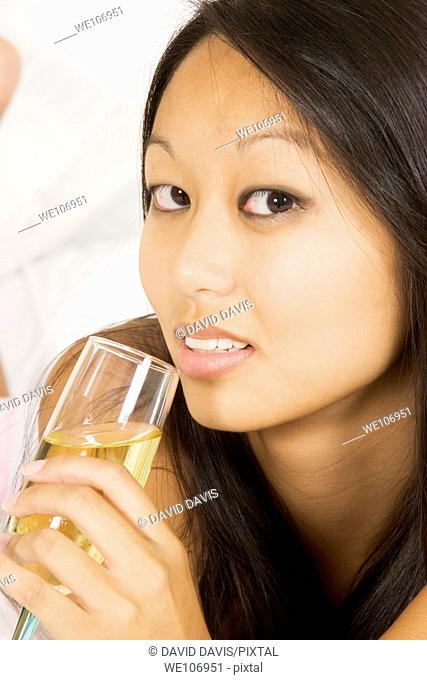 Asian woman in early 20's laying in bed drinking white wine