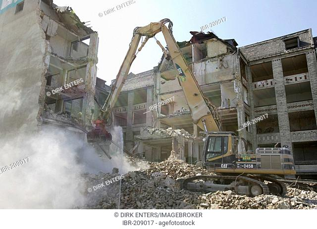 Digger knocks down an old apartment building in Berlin, Germany, Europe