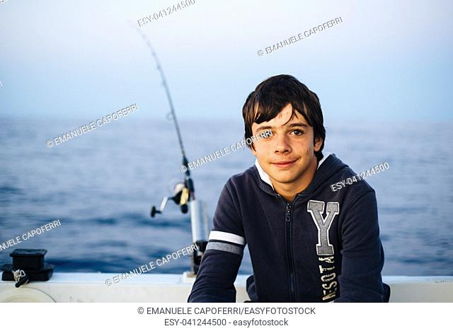 portrait of boy fisherman in boat in the sea with fishing rod in the background