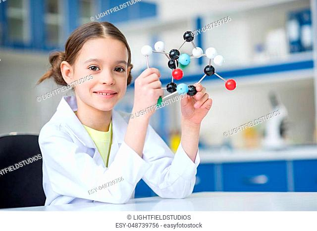 Girl scientist in lab coat holding molecular model and smiling at camera