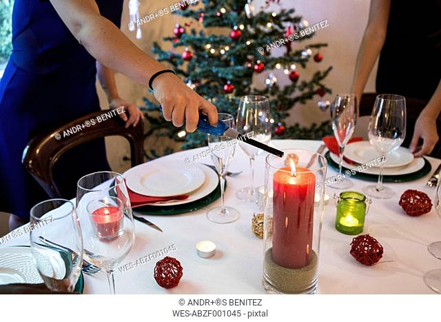 Woman lighting a candle on Christmas dinner table