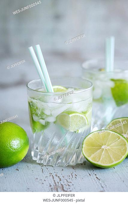 Glasses of infused water with lime and ice cubes