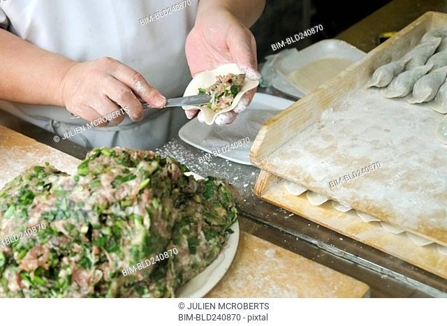 Chef spreading filling in dumpling