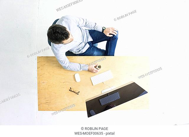 Businessman sitting at desk in office seen from above