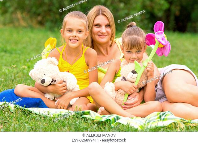 Young mother sitting on a picnic in a clearing with two daughters