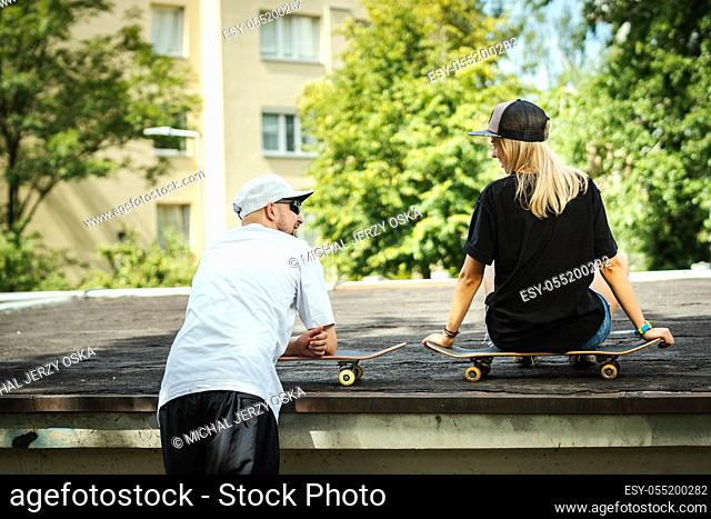 boy and girl on a skateboard are talking with each other on a summer day