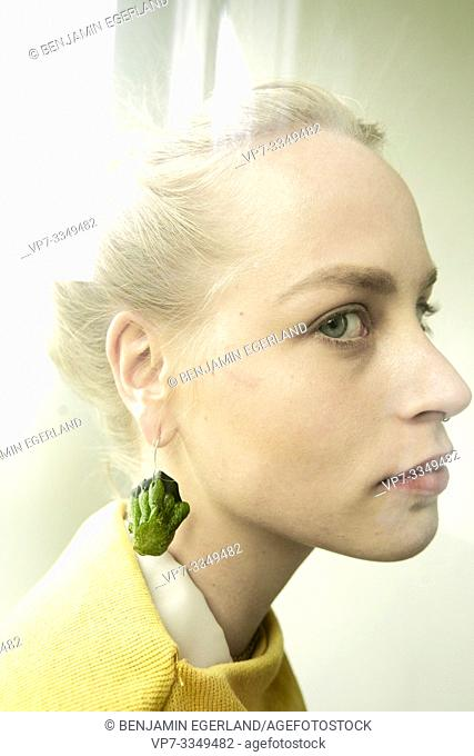 young thoughtful woman wearing earring made of raw zucchini