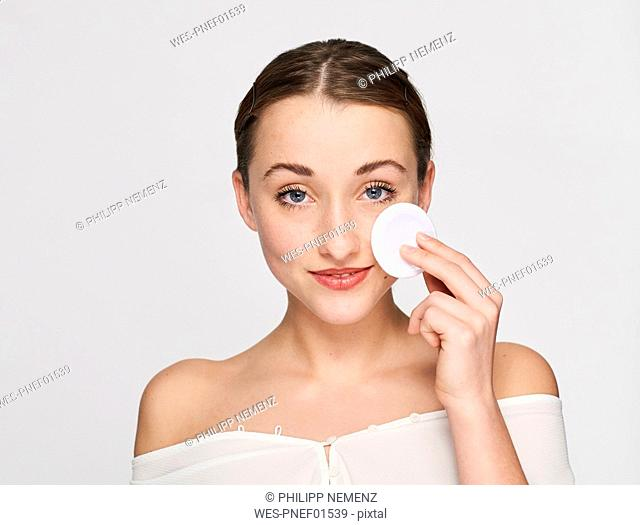 Portrait of smiling young woman with cotton pad