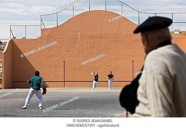 France, Pyrenees Atlantiques, Saint Jean de Luz, man watching a Basque pelota match played in a wall called fronton