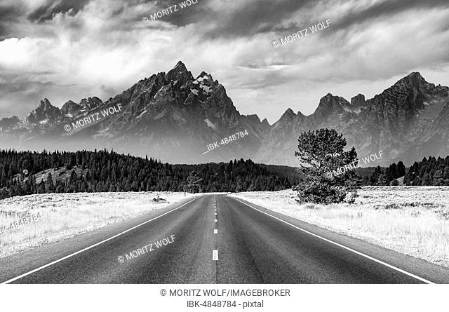 Black and white, country road in front of rugged mountains with cloudy skies, Grand Teton Range, Grand Teton National Park, Wyoming, USA