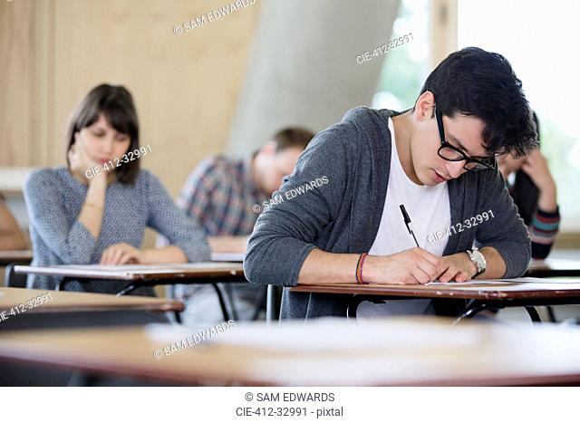 Focused male college student taking test at desk in classroom