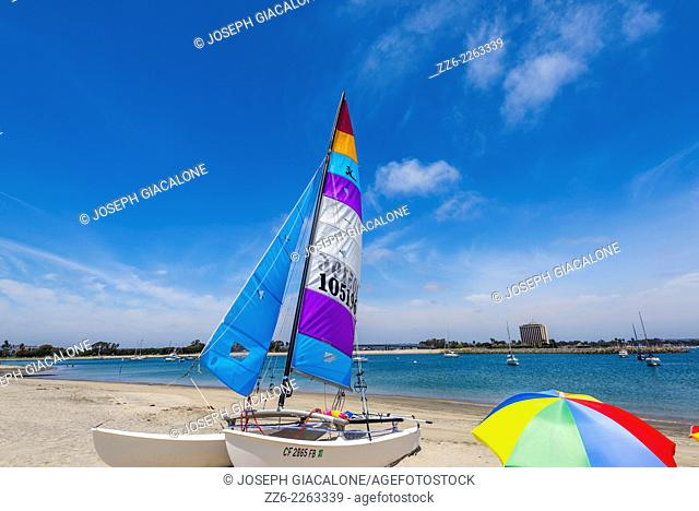 Sailboat and colorful umbrella at Misison Bay Park. San Diego, California, United States