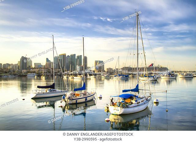 Three sail boats with a glassy reflection on San Diego Bay at sunrise
