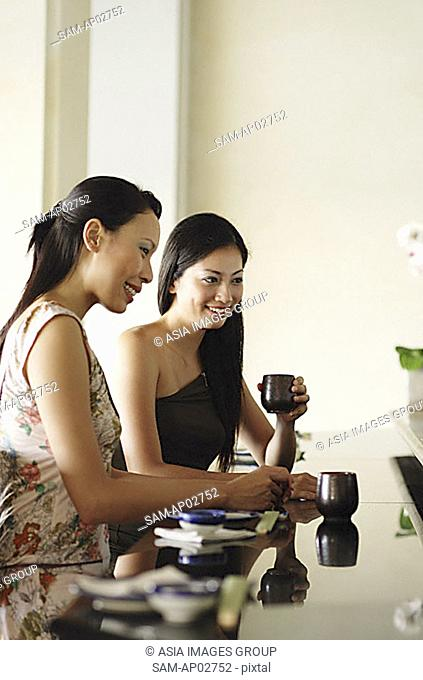 Women sitting at table, side by side, having chinese tea