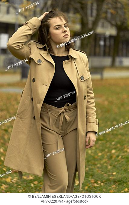 young woman walking outdoors in park during autumn season, ruffling hair, wearing coat, prankish, coquettish, individual fashion style, in Munich, Bavaria