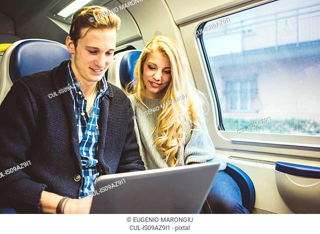Young couple typing on laptop whilst travelling in train carriage, Italy