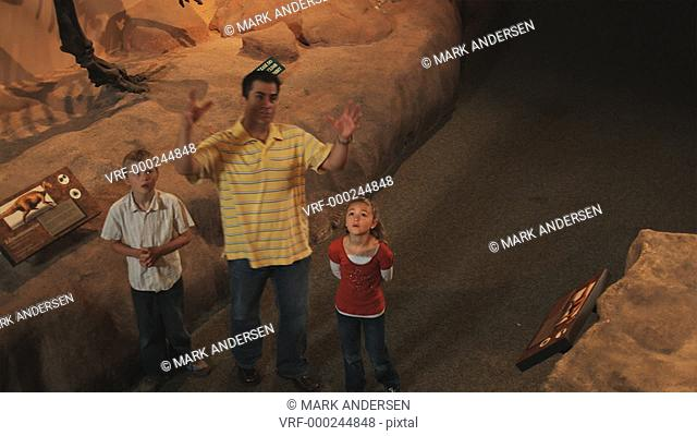 MS HA Man with daughter (8-9) and son (10-11) in natural history museum, dinosaur's teeth in foreground, Lehi, Utah, USA