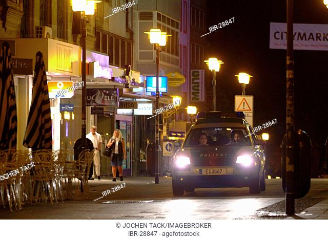 DEU, Germany, Essen: Police car at a night patrol drive in the city center, railway station. Daily police life. Officer from a city police station