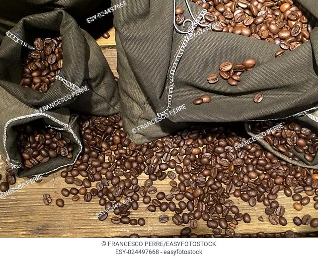coffee beans on bags over rustic wood background