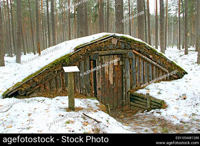 Partisan dugout in winter forest. Earth-house built by Soviet partisans in Ukrainian forest during Secont World War. War museum in forest