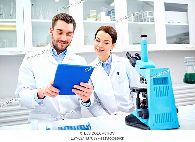 science, chemistry, technology, biology and people concept - young scientists with tablet pc and microscope making test or research in clinical laboratory