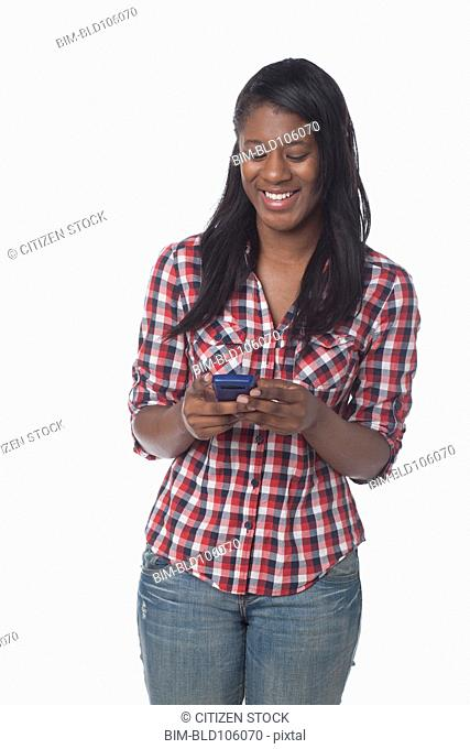 Mixed race woman text messaging on cell phone