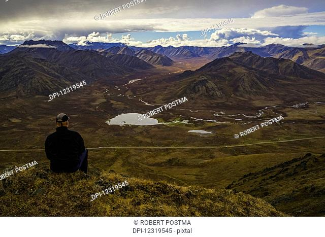 Man stitting on a look out overlooking the Blackstone Valley, along the Dempster Highway; Yukon, Canada