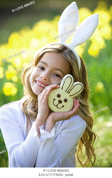 A young girl holding a chocolate bunny, wearing bunny ears